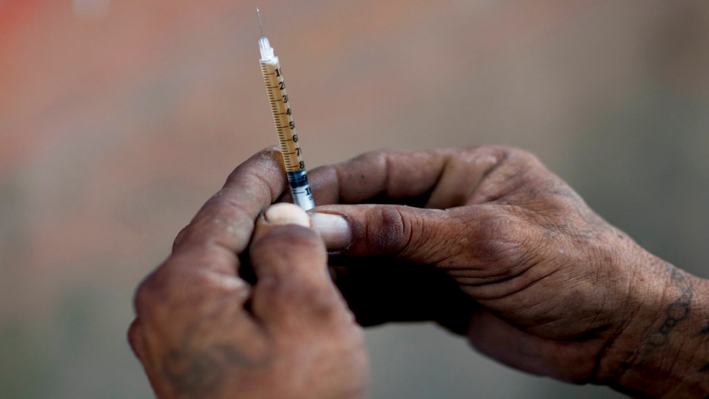 In this Dec. 14, 2018 photo, a heroin addict prepares a dose for himself, in an area where heroine uses shoot up behind an abandoned home in Humacao, Puerto Rico. An opioid problem is growing in Puerto Rico even as the U.S. territory struggles to cope with an economic crisis and the devastation caused by Hurricane Maria. (AP Photo/Carlos Giusti)