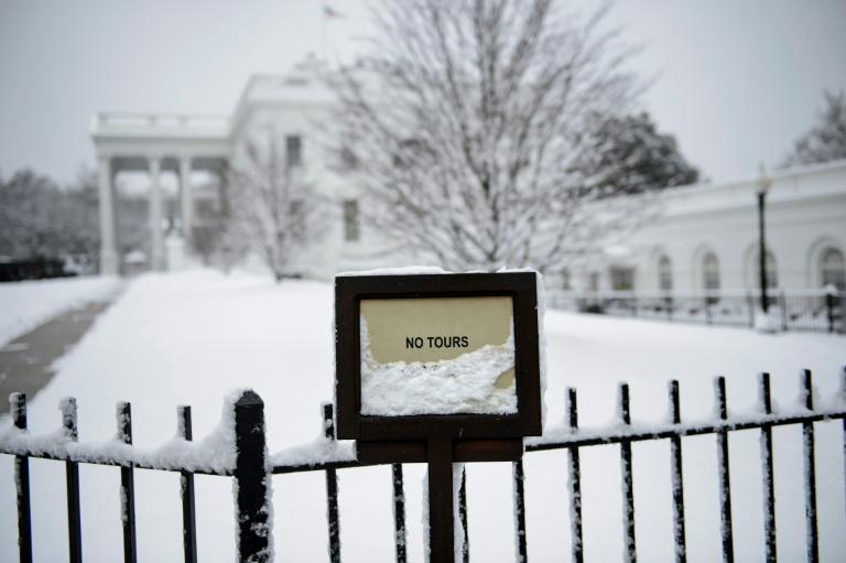 Un membre des services secrets américains devant la Maison Blanche enneigée le dimanche 13 janvier 2019 à Washington