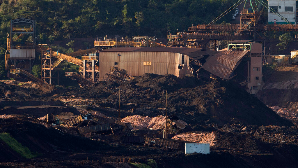 A destroyed facility and wagons stand in ruins after a dam collapsed two days prior, next to dam B6 that was at risk of breach as well, in Brumadinho, Brazil, Sunday, Jan. 27, 2019. Authorities evacuated several neighborhoods in the southeastern city of Brumadinho that were within range of the B6 dam owned by the Brazilian mining company Vale. (AP Photo/Leo Correa)