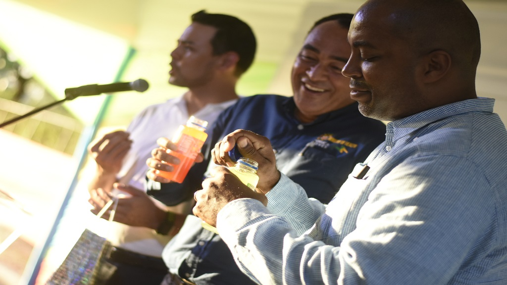 Health Minister, Dr Christopher Tufton (centre), and South East St Andrew Member of Parliament, Julian Robinson (right), in a lighthearted exchange during the recent launch of the new Big Jo Z drink line. Also pictured in the background is an executive of Coldfield Manufacturing, which produces Big Jo drinks among other beverage brands. (Photos: Marlon Reid)