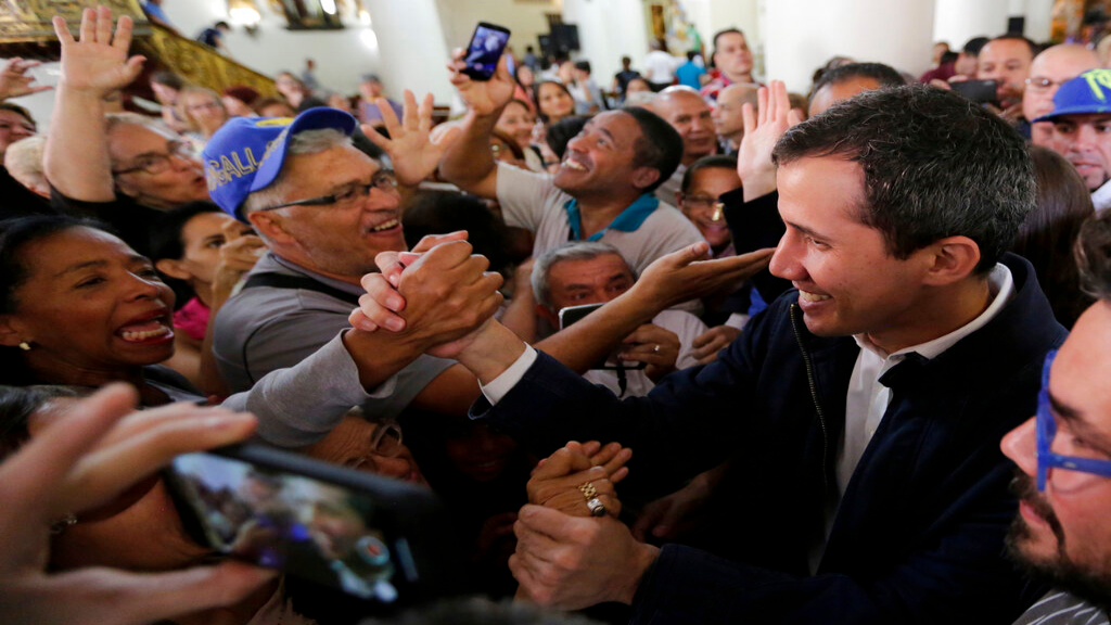 Opposition National Assembly leader Juan Guaido, right, who declared himself interim president, greets supporters as he leaves church after attending Mass in Caracas, Venezuela, Sunday, Jan. 27, 2019. Guaido says he is acting in accordance with two articles of the constitution that give the National Assembly president the right to hold power temporarily and call new elections. (AP Photo/Fernando Llano)
