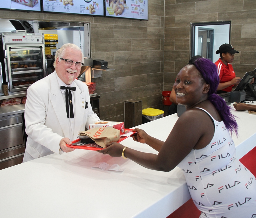 Decked out in his iconic white suit, the Colonel jumped right into assisting KFC team members with serving up KFC chicken. (Photo: Contributed)