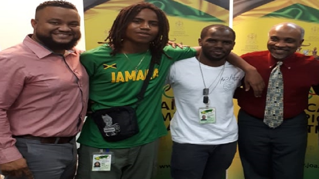 Ryan Foster (left) president of Skateboarding Jamaica Limited and Christopher Samuda (right), president of Jamaica Olympic Association, pose with skaters Taffari Whitter (2nd left) and Mario Notice (3rd left).