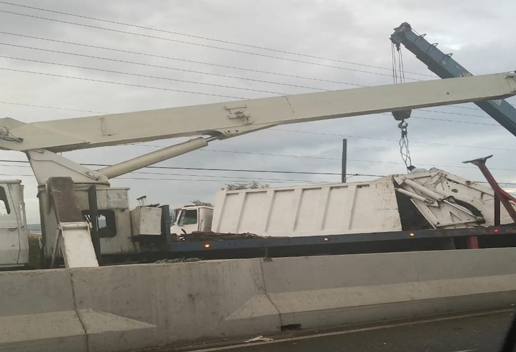 A wrecker hoists a truck that overturned along Marcus Garvey Drive in Kingston on Wednesday.