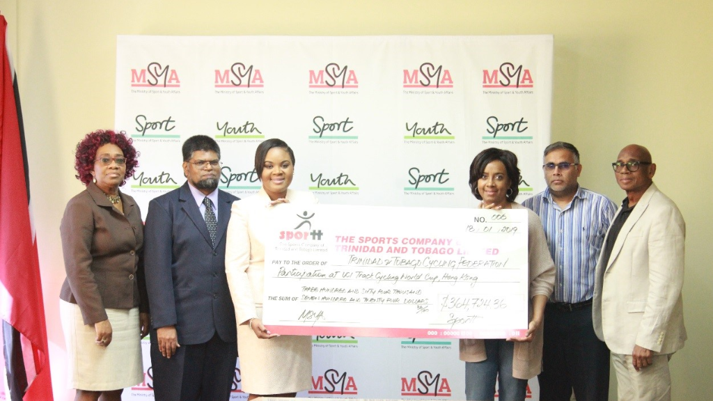 The Honourable Shamfa Cudjoe, Minister of Sport and Youth Affairs presents a cheque to Ms. Jacqueline Corbin,