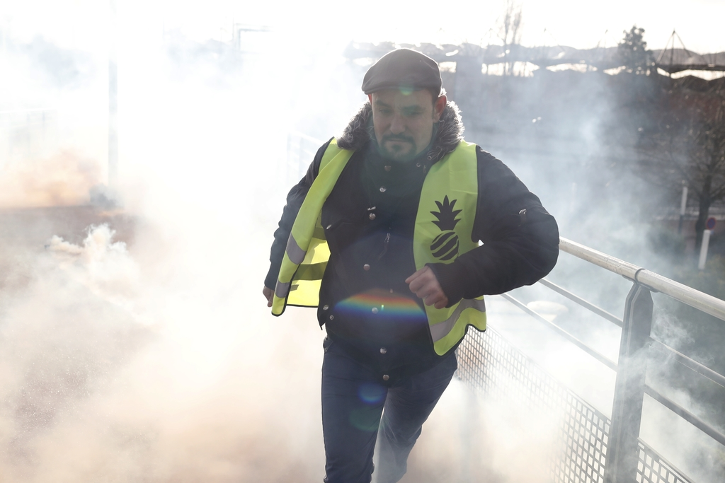 A protestor runs from teargas launched by riot police during a demonstration of unionist and yellow vests, in Creteil, outside Paris, Wednesday. (AP Photo)