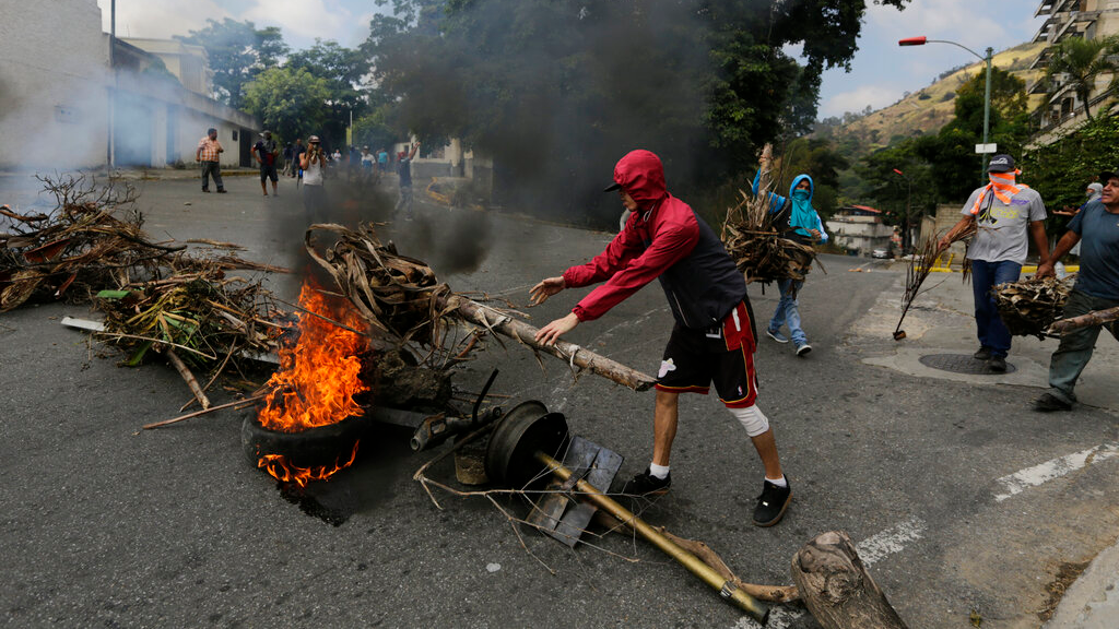 Anti-government protesters face off with security forces as they show support for an apparent mutiny by a national guard unit in the Cotiza neighborhood of Caracas, Venezuela, Monday, Jan. 21, 2019. (AP Photo/Ariana Cubillos)