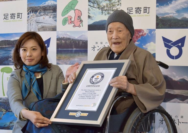 Masazo Nonaka (D), alors âgé de 112 ans, sourit en recevant son certificat d'homme le plus âgé du monde des mains d'Erika Ogawa (G), vice-présidente au Japon du Guinness des records, à Ashoro dans la préfecture d'Hokkaido le 10 avril 2018