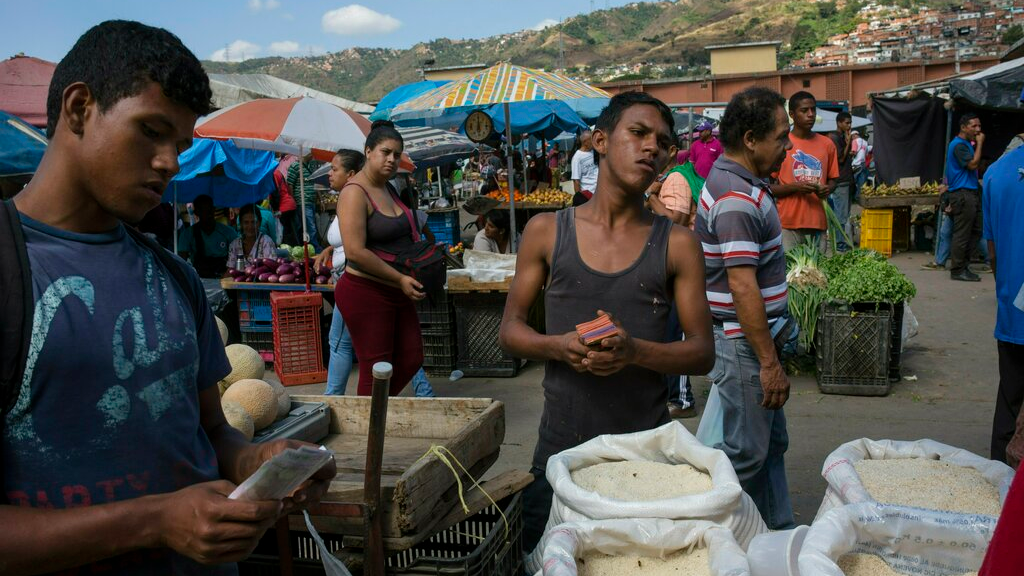 Workers wait for customers at their vegetable stand at a wholesale food market in Caracas, Venezuela, Monday, Jan. 28, 2019. Economists agree that the longer the standoff between the U.S.-backed opposition leader Juan Guaido and President Nicolas Maduro drags on, the more regular Venezuelans are likely to suffer. (AP Photo/Rodrigo Abd)