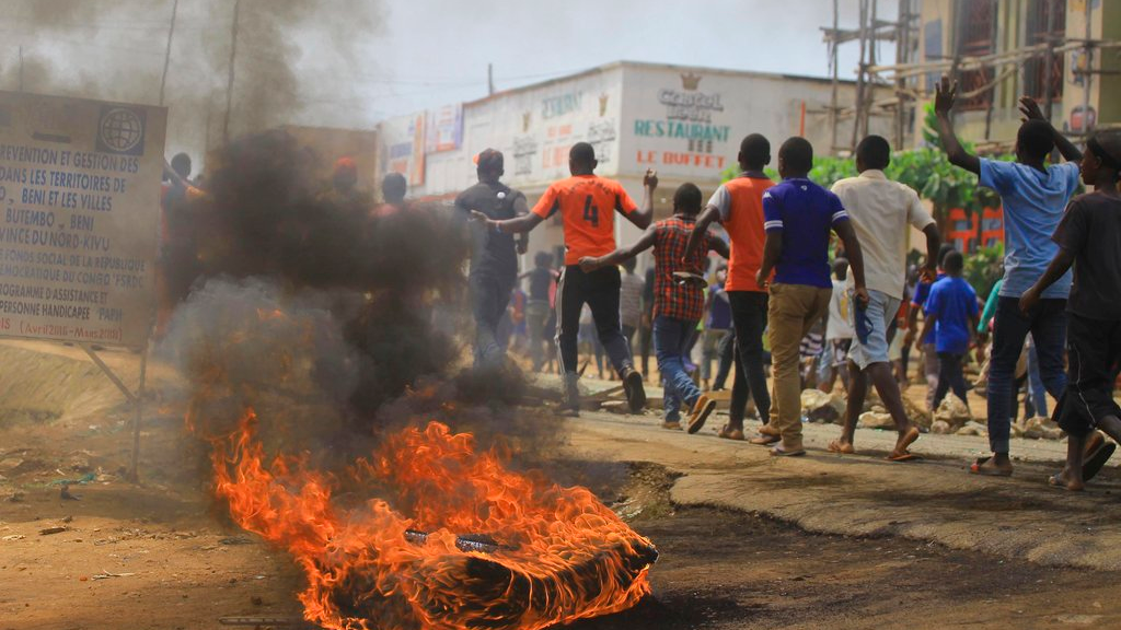 Protesters walk past a burning tyre in the Eastern Congolese town of Beni, Friday Dec. 28, 2018, as they demonstrate against the election postponed until March 2019, announced by Congo's electoral commission for Beni residents that is blamed on a deadly Ebola outbreak. (AP Photo/Al-hadji Kudra Maliro)