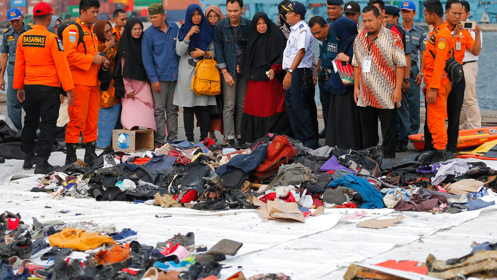 In this Oct. 31, 2018, file photo, relatives of passengers of a crashed Lion Air jet check personal belongings retrieved from the waters where the airplane is believed to have crashed, at Tanjung Priok Port in Jakarta, Indonesia.