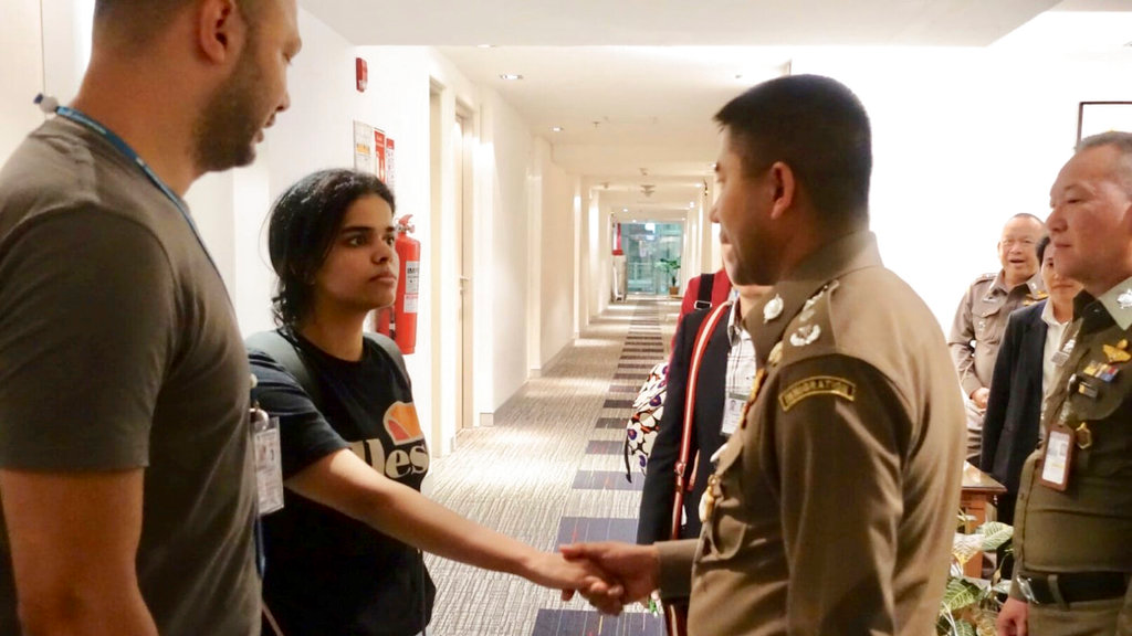 In this photo released by the Immigration Police, Saudi woman Rahaf Mohammed Alqunun, second left, shakes hand with Chief of Immigration Police Maj. Gen. Surachate Hakparn before leaving the Suvarnabhumi Airport in Bangkok Monday, Jan. 7, 2019.