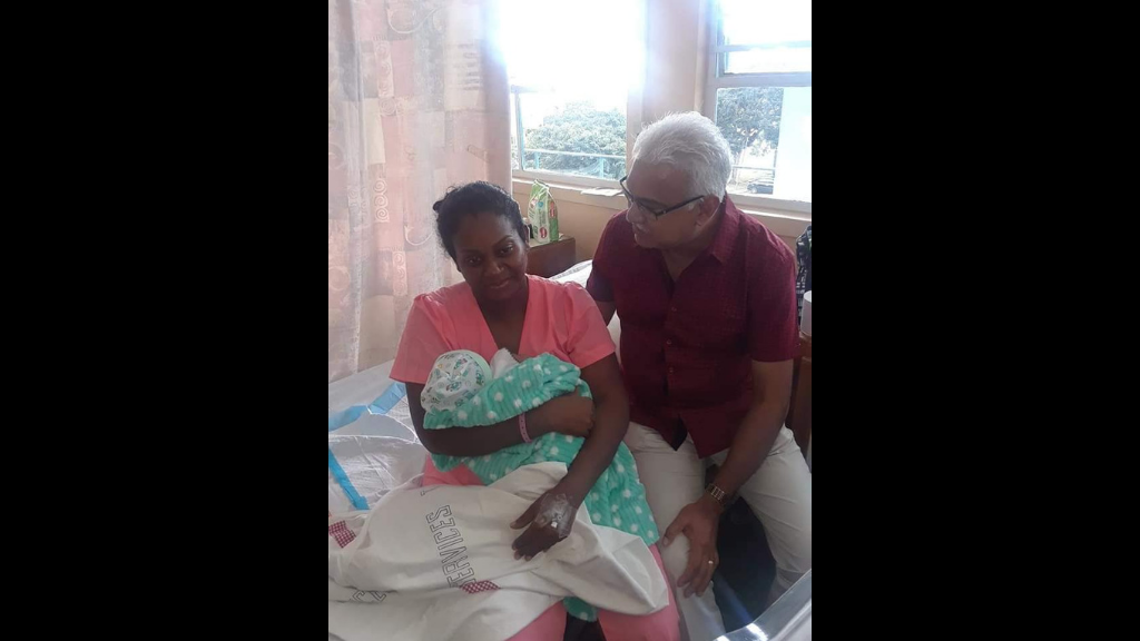 New Year's baby: Health Minister Terrence Deyalsingh looks on as a mother