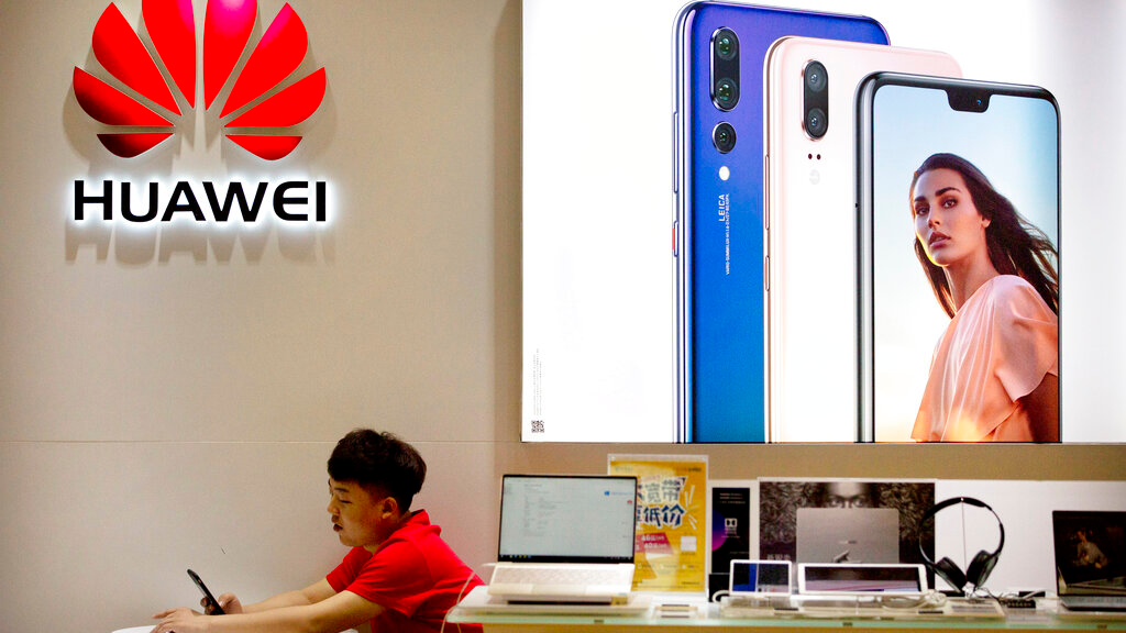In this July 4, 2018, file photo, a sales clerk looks at his smartphone in a Huawei store at a shopping mall in Beijing. (AP Photo/Mark Schiefelbein, File)