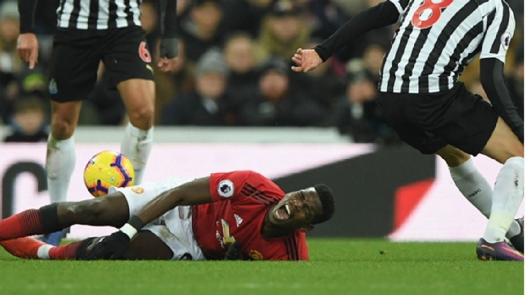 Manchester United midfielder Paul Pogba grimaces on the turf following a rash tackle from Newcastle United midfielder Jonjo Shelvey.
