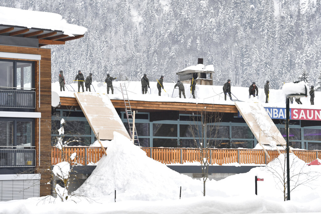 Solidiers from the Austrian Bundesheer clean a roof from snow on Saturday, Jan. 12, 2019 in Waidring. Austrian province of Tyrol.(AP Photo/Kerstin Joensson)