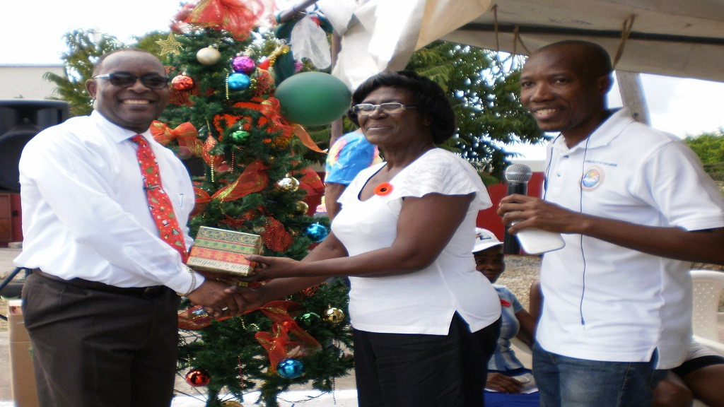 Mayor Leon Thomas (left) presents a gift to a pensioner during the annual Christmas treat of the Portmore Municipal Corporation. Also in photo is Courtney Edwards, Councillor for the Independence City division.