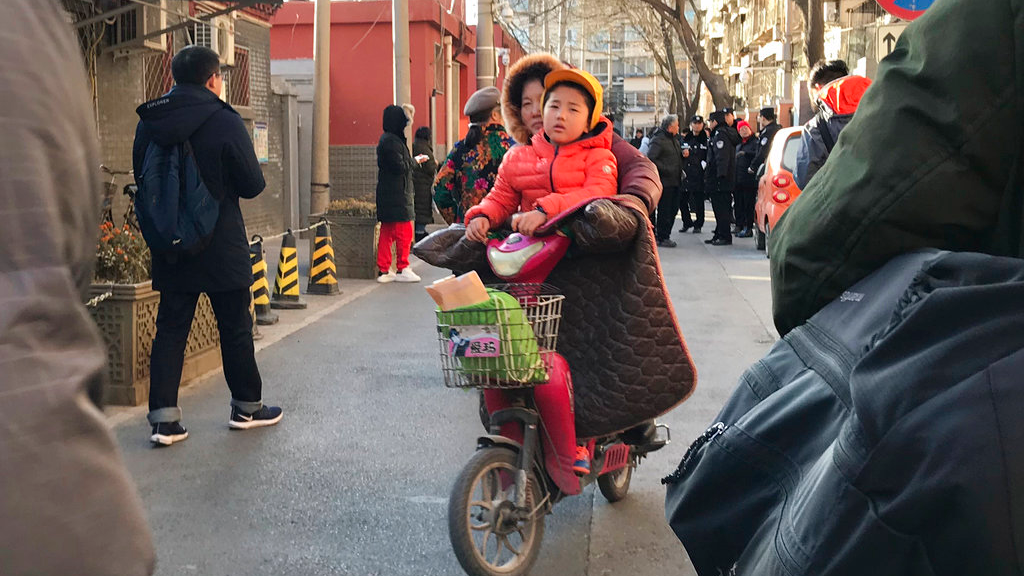 A woman and child leave the Beijing No. 1 Affiliated Elementary School of Xuanwu Normal School following an attack in Beijing, China, Tuesday, Jan. 8, 2019. A male attacker injured 20 children Tuesday inside the primary school in China's capital, officials said. (AP Photo/Ng Han Guan)