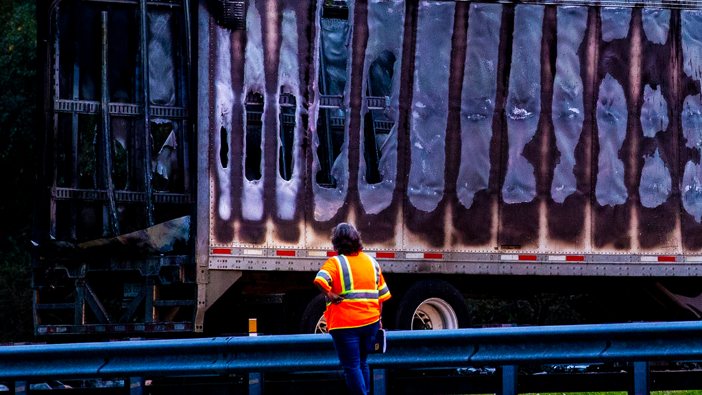 A worker looks at a charred semi-truck after a wreck with multiple fatalities on Interstate 75, south of Alachua, near Gainesville, Fa., Thursday, Jan. 3, 2019.