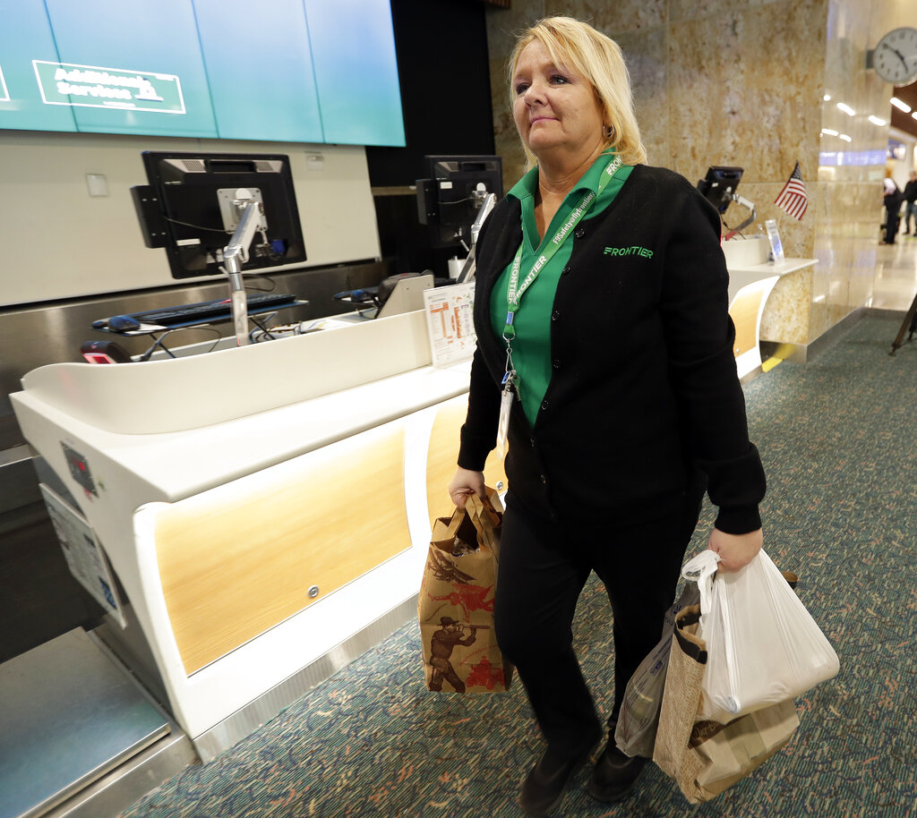 Chantele Montover, a counter agent with Frontier Airlines, takes food donations to a distribution point for to be given to TSA workers at Orlando International Airport Tuesday, Jan. 15, 2019, in Orlando, Fla. Florida airports are helping federal workers who aren't getting paid during the government shutdown by offering free food, holding a food drive and opening a food bank. (AP Photo/John Raoux)