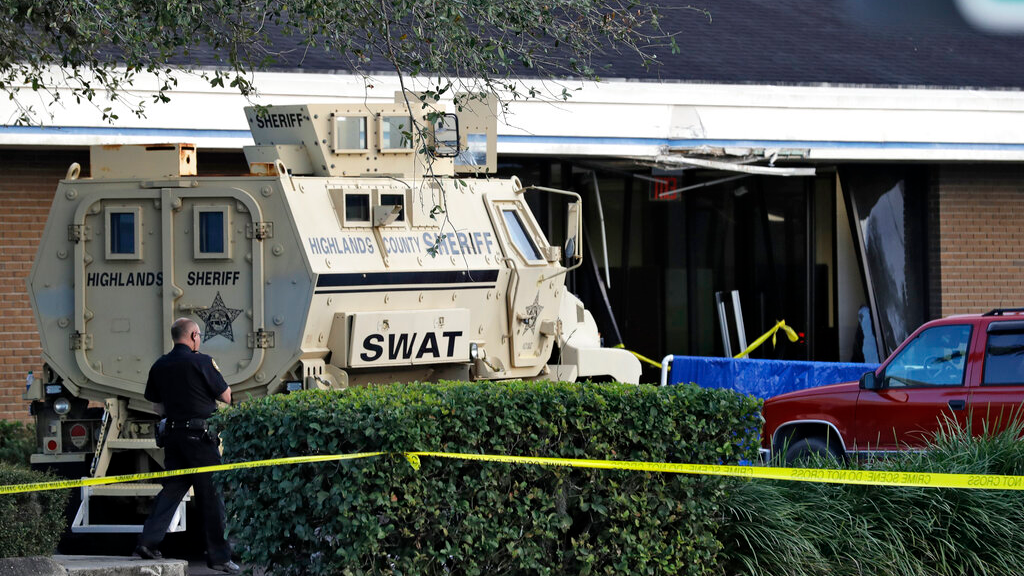 A Sebring, Fla., police officer stands near a Highlands County Sheriff's SWAT vehicle that is stationed in front of a SunTrust Bank branch, Wednesday, Jan. 23, 2019, in Sebring, Fla., where authorities say five people were shot and killed. (AP Photo/Chris O'Meara)
