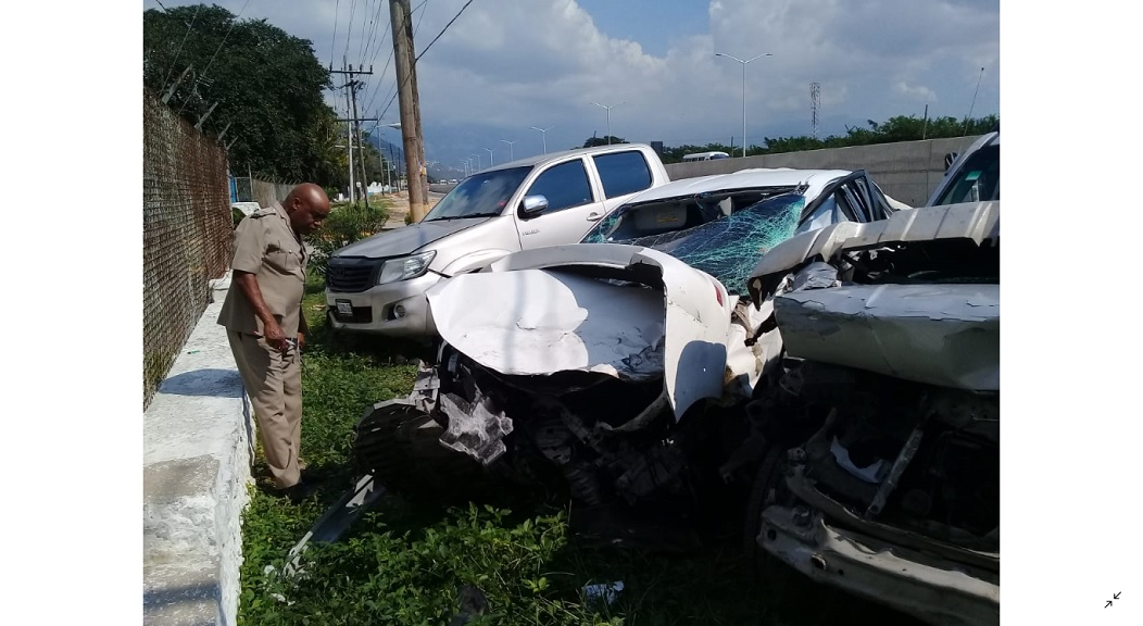 A police officer inspects one of the vehicles that was damaged in the three way collision on Mandela Highway.