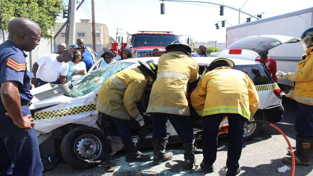 Firefighters work to extricate a woman from the mangled taxi in downtown Kingston on Monday morning.