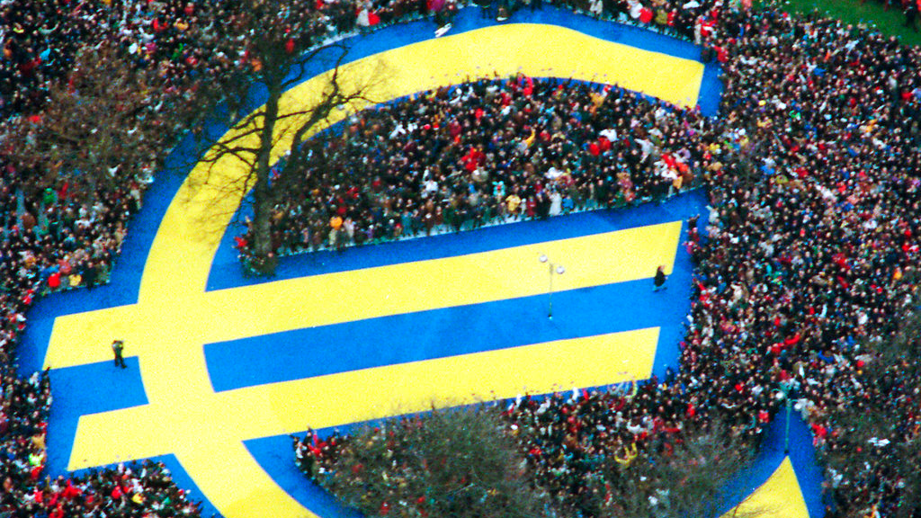 In this Friday, Jan. 1, 1999 file photo, thousands of people stand around a huge Euro symbol displayed in a park in Frankfurt's banking district on the day of the launch of the Euro, the European single currency, officially adopted in 11 European states. (AP Photo/Bernd Kammerer, File)