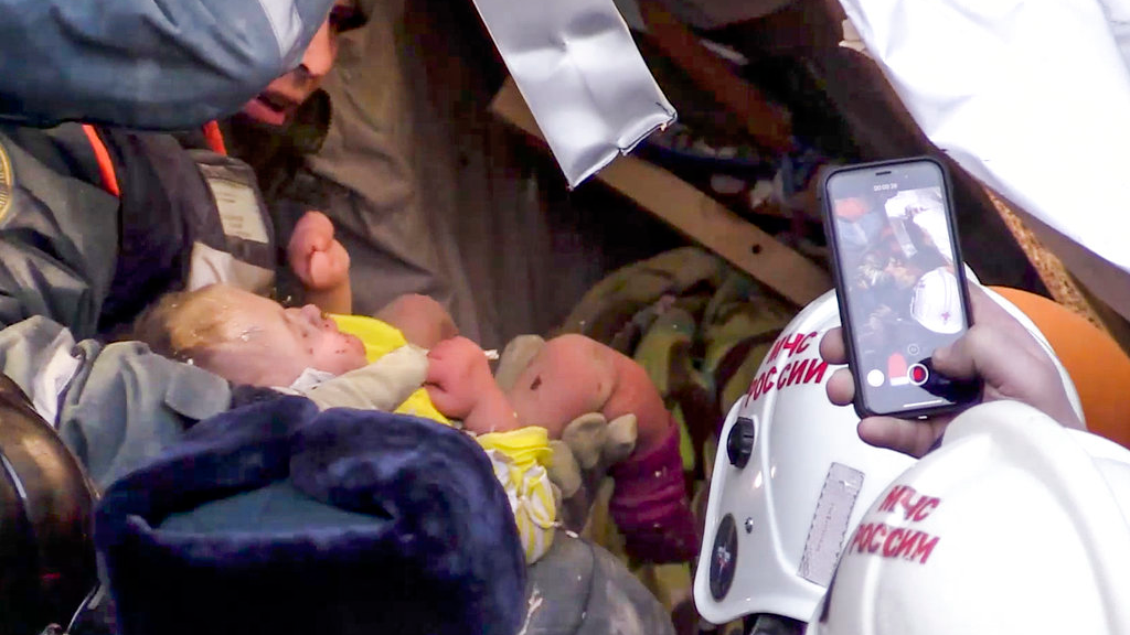 This photo provided by the Russian Emergency Situations Ministry taken from TV footage shows Emergency Situations employees save a 10-month-old baby at the scene of a collapsed section of an apartment building, in Magnitigorsk, a city of 400,000 about 1,400 kilometres (870 miles) southeast of Moscow, Russia, Tuesday, Jan. 1, 2019.