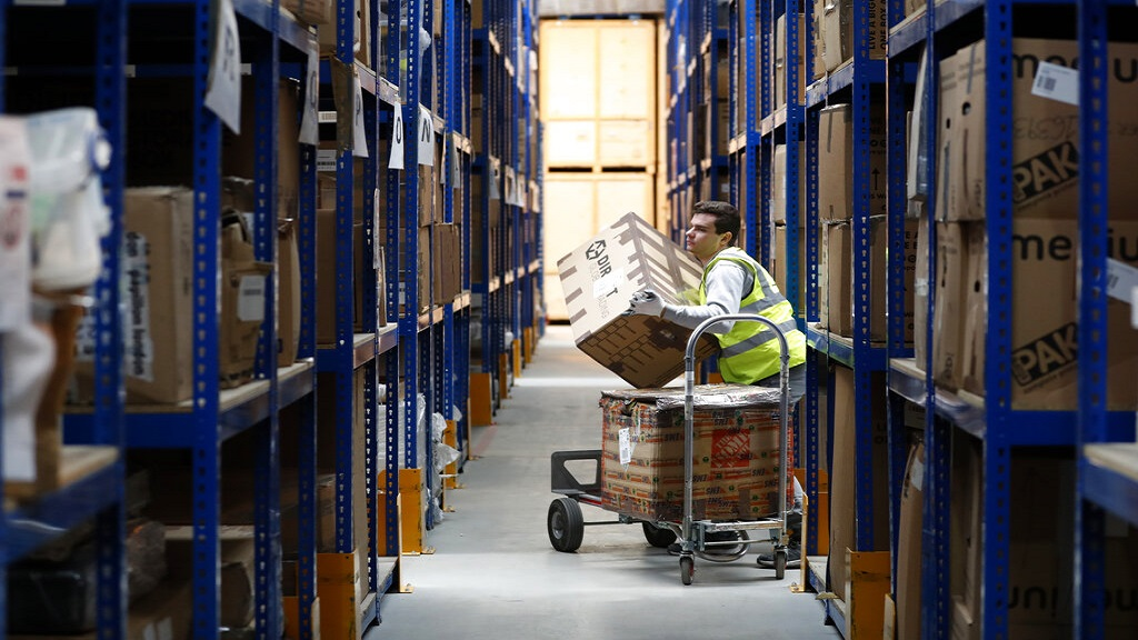 Lovespace warehouse worker Pawel Mazur unloads boxes from a trolley to place them into their allocated zones at the warehouse in Dunstable, England. (AP Photo)