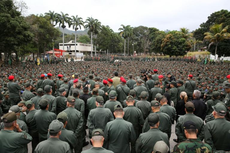 """Le président vénézuélien fait le """"V"""" de la victoire en compagnie de militaires, le 30 janvier 2019 à Caracas. AFP PHOTO - Venezuelan Presidency / Marcelo GARCIA"""
