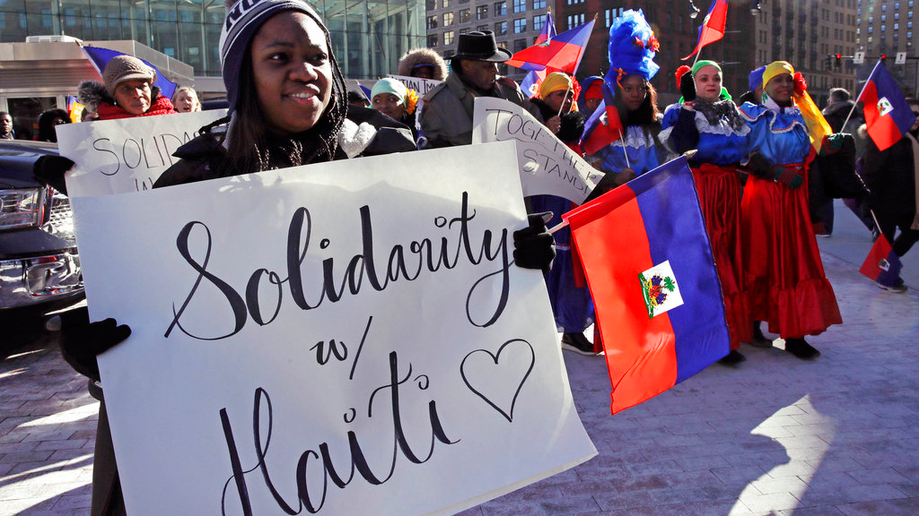 In this Jan. 26, 2018 file photo, Haitian activists and immigrants protest on City Hall Plaza in Boston. A trial in New York over the Trump administration's move to cut off permission for thousands of Haitians to live in the U.S. is spotlighting emails between officials downplaying health and safety crises in the Caribbean nation as they tried to justify the change. (AP Photo/Charles Krupa, File)