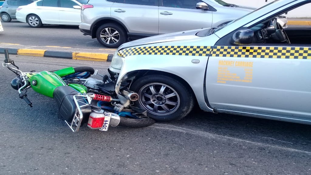 This collision between a motorcycle and a Toyota Probox motor car led to four other vehicles colliding along Trafalgar Road on Monday morning. (PHOTOS: Llewellyn Wynter)