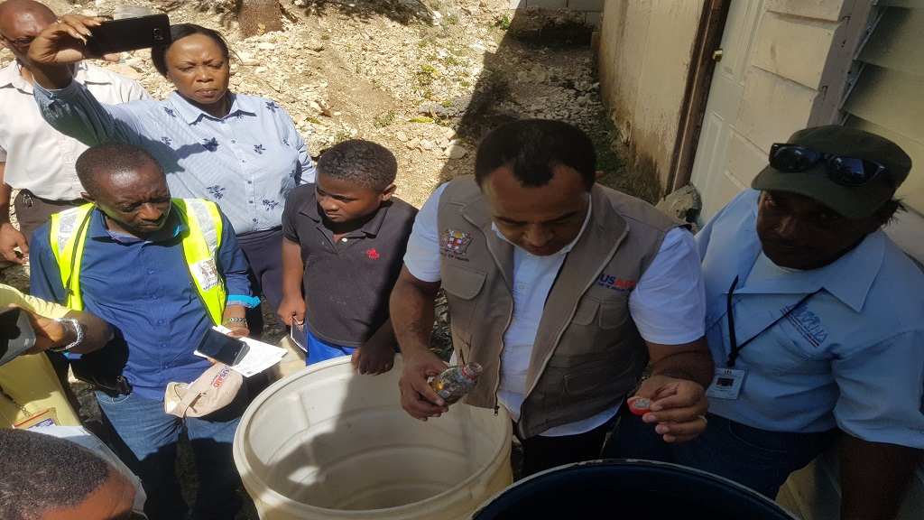 Health Minister, Dr Christopher Tufton (second right) treating stored water during a tour of Westmoreland on Friday to get a firsthand account of the parish's vector control plans in the wake of the ongoing dengue fever outbreak nationally.