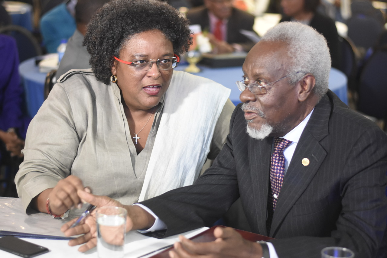 Former Prime Minister PJ Patterson listens as Barbados Prime Minister Mia Mottley makes a point at the JSE's Regional Investments and Capital Markets Conference.