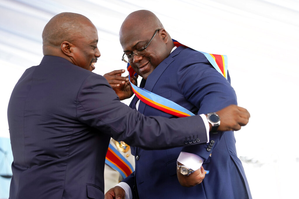 Congolese President Felix Tshisekedi, right, receives the presidential sash from outgoing president Joseph Kabila after being sworn in in Kinshasa, Democratic Republic of the Congo, Thursday Jan. 24, 2019. (AP Photo/Jerome Delay)