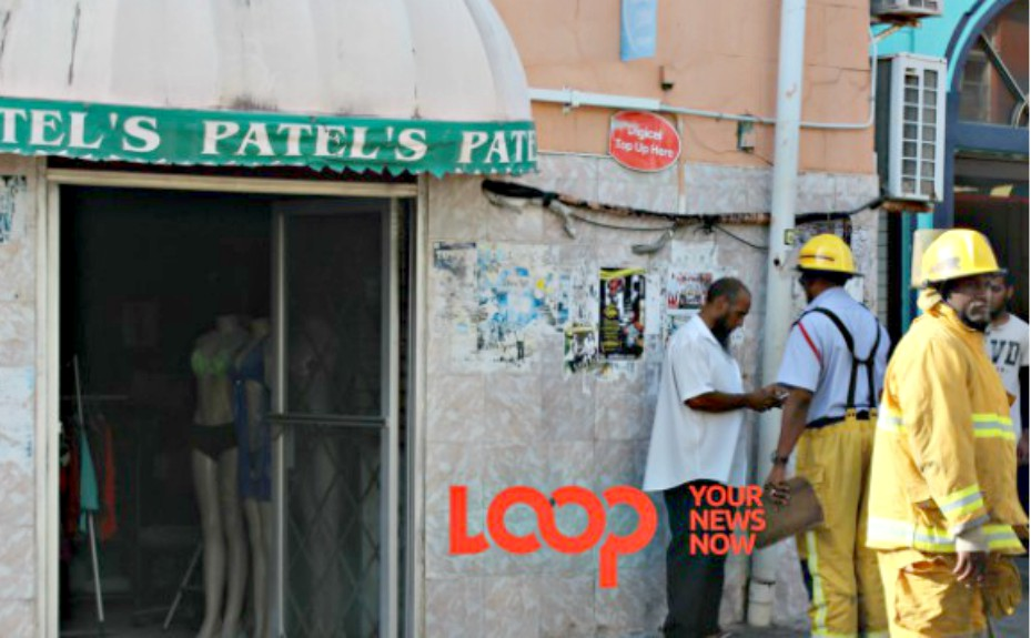 Mohammed Patel  (in white) speaking to fire officers outside his clothing store.