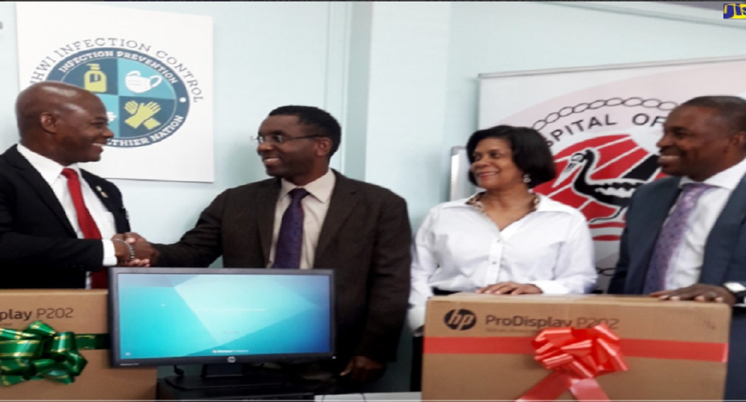 Chief Executive Officer of the Universal Service Fund (USF), Daniel Dawes (left), officially hands over a new infection control surveillance system to Chief Executive Officer at the University Hospital of the West Indies (UHWI), Kevin Allen (second left), during a ceremony at the hospital's Papine location. Sharing the moment are head of Microbiology and Chair of the Infection Control Committee, Dr. Allison Nicholson (second right), and Medical Chief of Staff at UHWI, Dr. Carl Bruce.