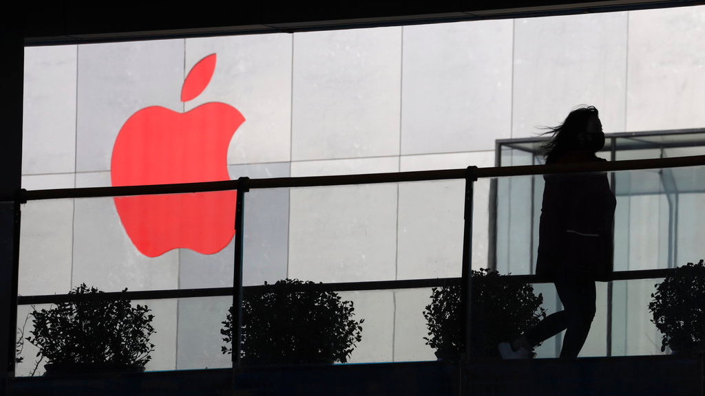 In this Dec. 6, 2018, photo, a woman runs past a Apple logo colored red in Beijing, China. Apple Inc.'s $1,000 iPhone is a tough sell to Chinese consumers who are jittery over an economic slump and a trade war with Washington.