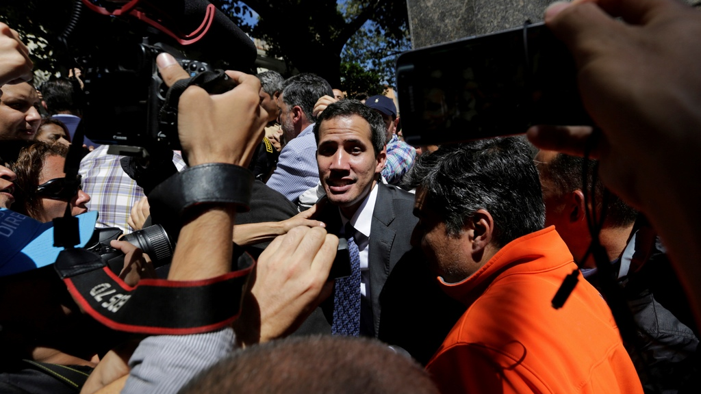 Supporters of opposition leader Juan Guaido and the press gather around him as he leaves a public plaza where he spoke in Caracas, Venezuela, Friday, Jan. 25, 2019. The 35-year-old lawmaker's whereabouts had been a mystery since he was symbolically sworn in Wednesday before tens of thousands of cheering supporters, promising to uphold the constitution and rid Venezuela of Maduro's dictatorship. (AP Photo/Fernando Llano)