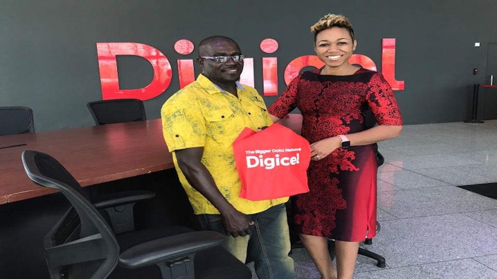 'Good Samaritan' Silbert Williams collects his reward from Katasha Thompson, head of operations, retail and distribution of Digicel. (PHOTO: Kimmo Matthews)