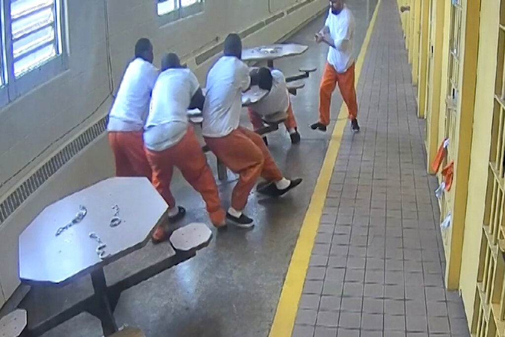 In this screenshot taken from a Southern Ohio Correction Facility security camera video four inmates, handcuffed to a table, are attacked by a fellow prisoner who slipped his handcuffs and brandished a knife, Sunday, June 4, 2017, at the Southern Ohio Correctional Facility in Lucasville, Ohio. (Southern Ohio Correction Facility via AP)