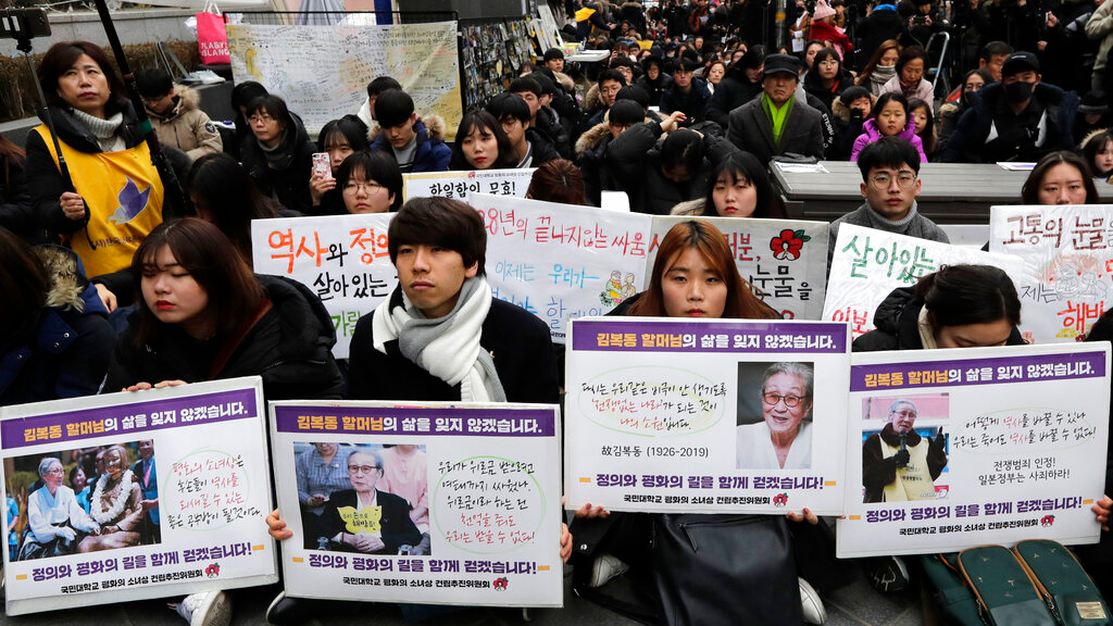Participants hold pictures of the deceased Kim Bok-dong, one of the many former South Korean sex slaves who were forced to serve for the Japanese military in World War II, during a weekly rally near the Japanese Embassy in Seoul, South Korea, Wednesday, Jan. 30, 2019.  (AP Photo/Lee Jin-man)