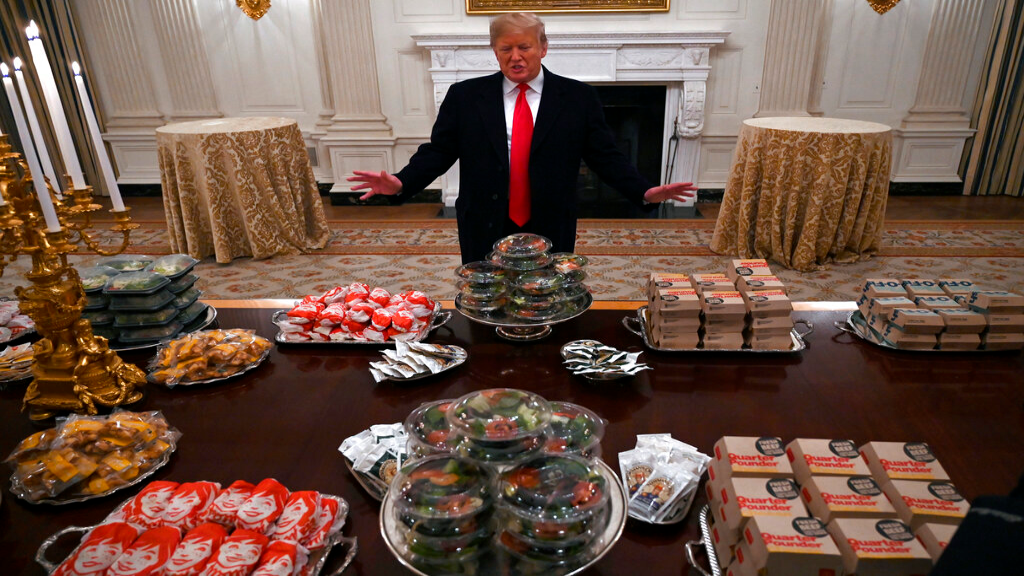 President Donald Trump talks to the media about the table full of fast food in the State Dining Room of the White House in Washington, Monday, Jan. 14, 2019, for the reception for the Clemson Tigers. (AP Photo/Susan Walsh)