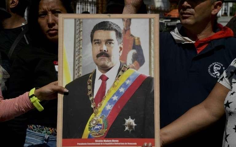 Des partisans du président vénézuélien Nicolas Maduro exhibent son portrait à Caracas, le 7 janvier 2019. AFP - YURI CORTEZ