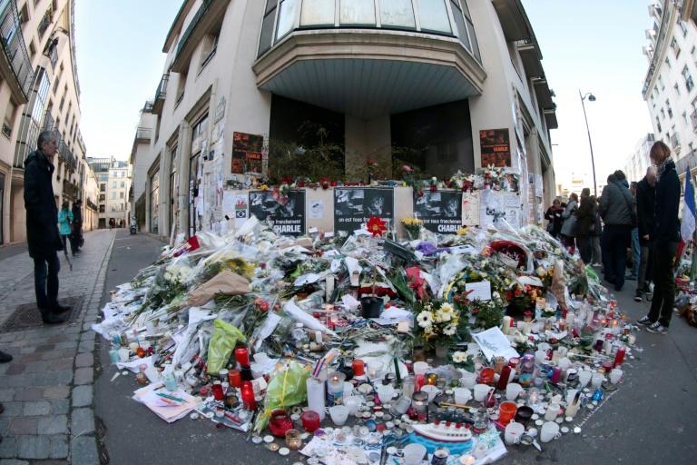 Des fleurs et des bougies sont déposées devant les locaux de Charlie Hebdo à Paris en hommage aux victimes de l'attentat, le 11 janvier 2015