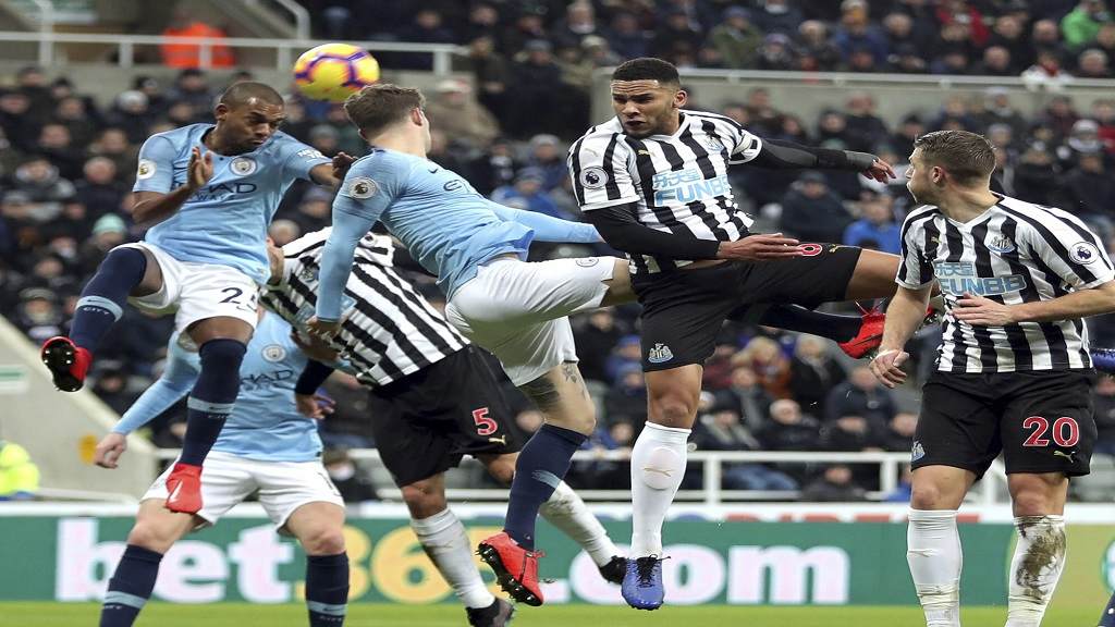 Newcastle United's Jamaal Lascelles, 2nd right, and Manchester City's John Stones, centre, in action for an aerial ball during their English Premier League football match at St James' Park in Newcastle, England, Tuesday Jan. 29, 2019.