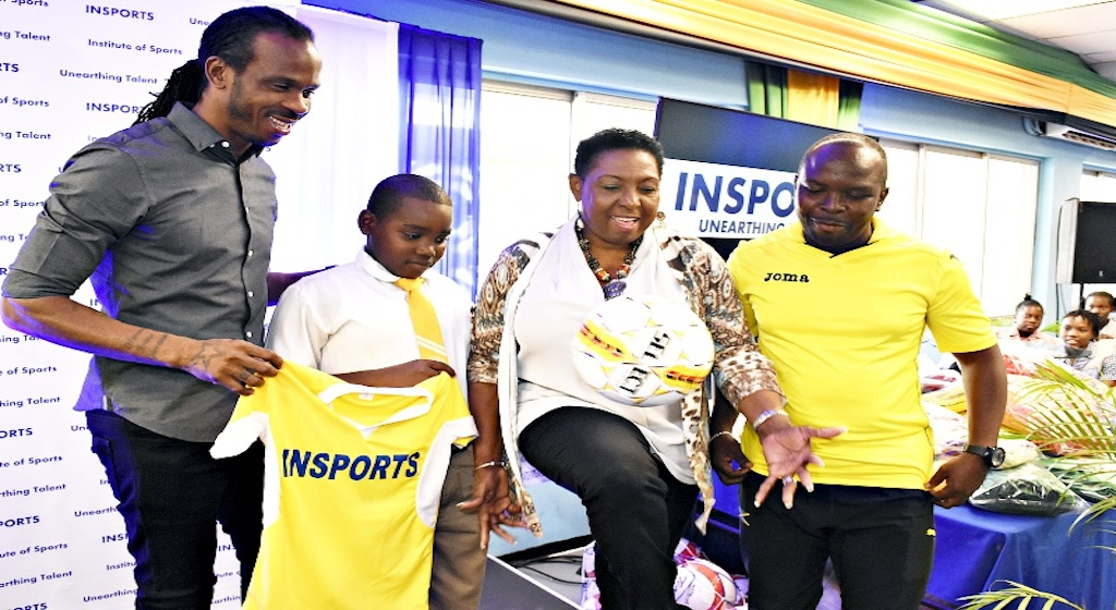 Sports Minister Olivia Grange (2nd right)  juggles a football before presenting McAuley Primary's coach Shane Richards (right) and player Nicardo Graham (2nd left) with team gear and match ball during the INSPORTS Primary School Football and Netball Round-of-16 Draw at the National Stadium Hospitality Room on January 11, 2019. Also looking on is former national player Ian 'Pepe' Goodison, who is the football ambassador of the competition.