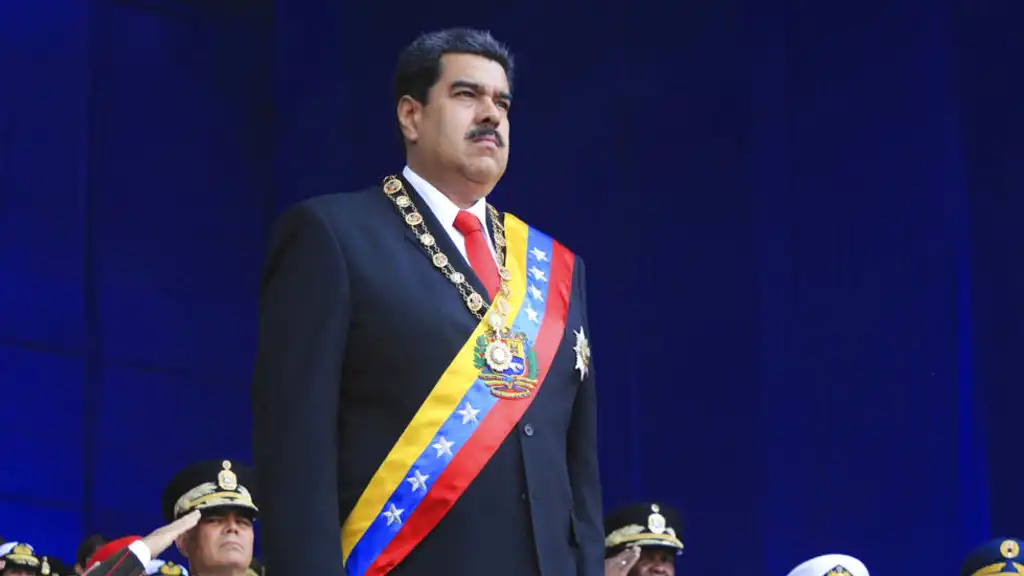 In this photo provided by the Miraflores Presidential Palace, President Nicolas Maduro stands at attention during a event marking the 81st anniversary of the National Guard, in Caracas, Venezuela, Saturday, August 4, 2018. (Miraflores Presidential Palace via AP)