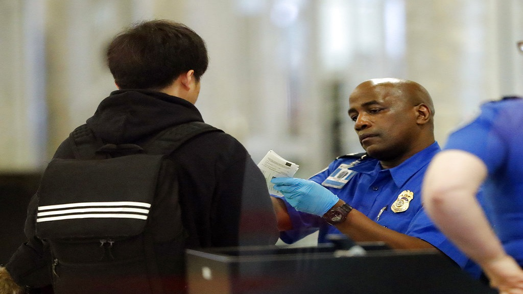 A Transportation Security Administration employee checks an air traveler's identification at Hartsfield Jackson Atlanta International Airport. (AP Photo)